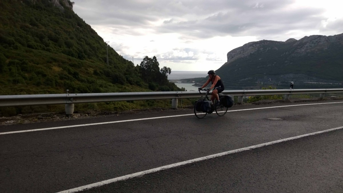Photograph of Sarah cycling along coast road with sea and mountains in the background.