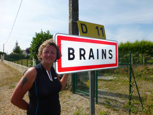 Photograph of Sarah standing next to sign for village of Brains in France.