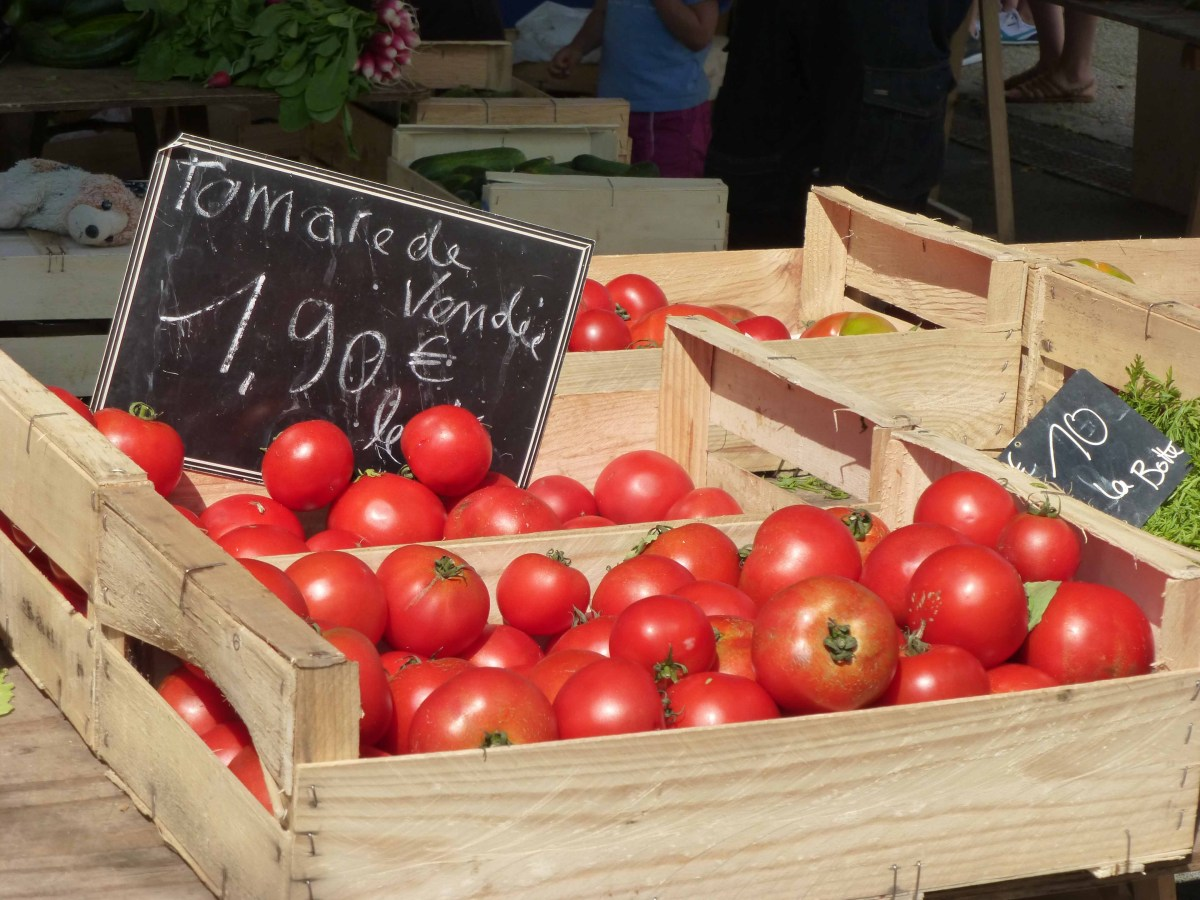 Photograph of a box of tomatoes on a French market stall.