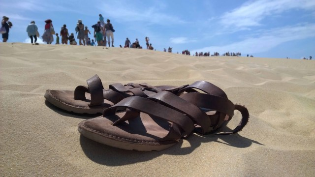 Photograph of brown leather sandals on top of sand dune.