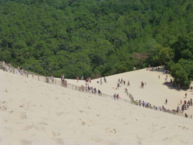 Photograph of Pyla huge sand dune with people climbing up it.