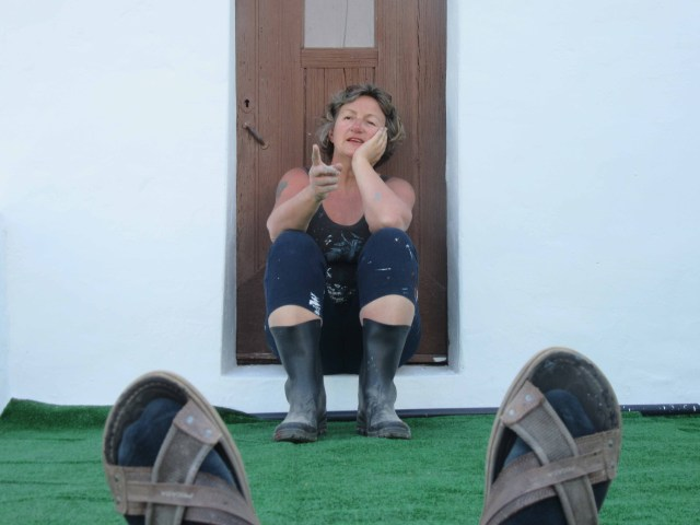 Photograph of Sarah Hendrickx sitting on the steps of Casa Torta with Keith Needham's feet in the foreground