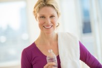 Woman With Water Bottle And Towel Smiling In Club