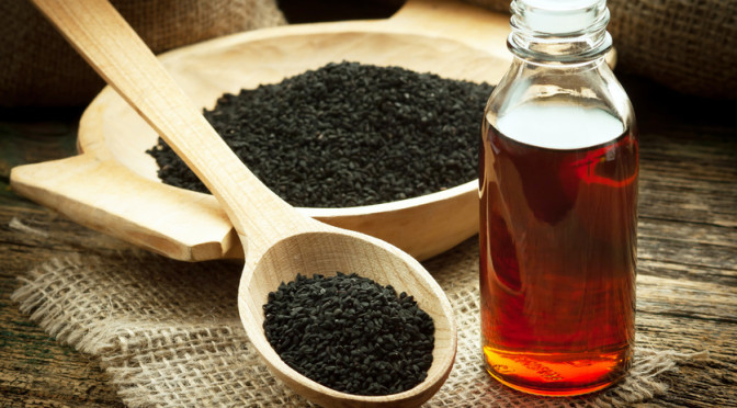 Nigella sativa (Black cumin) on wooden spoon and essential oil. Real oil from nigella looks like dark honey