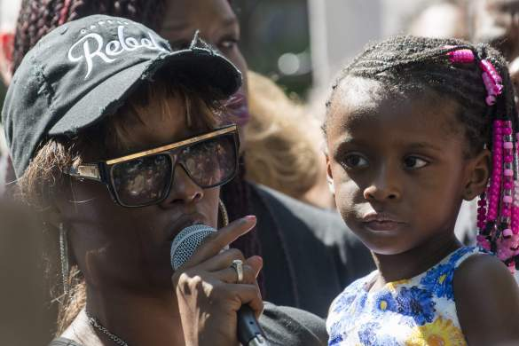 [Image description: Diamond Reynolds, a brown-skinned Black woman, wearing a frayed baseball cap and sunglasses, holds her 4-year-old daughter while speaking into a microphone. (Getty)