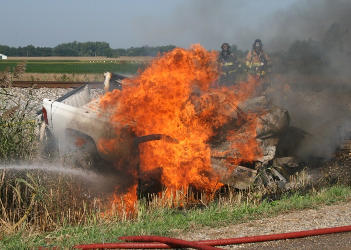Truck bursts into flames after crashing into train
