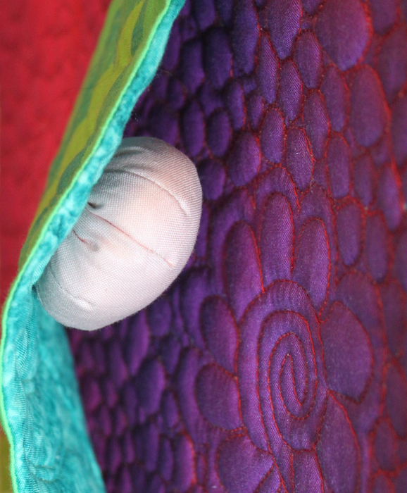 Egg or larvae in the metamorphosis of a butterfly quilted by doris lovadina-lee