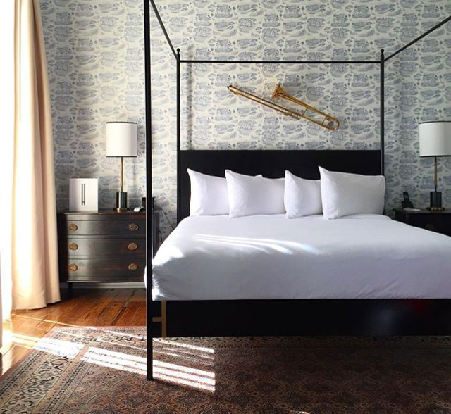 Henry Howard Hotel, New Orleans Louisiana features a four poster bed, blue and white toile wallpaper and a trombone as decor | Gather Goods Co