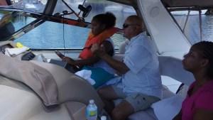 Dan Bradbary assists ZaNyah Hayes, 9, with driving the boat along the Intracoastal Waterway.