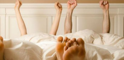 Man and woman in bed celebrating