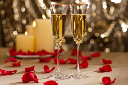 Romantic table setting with champagne and petals
