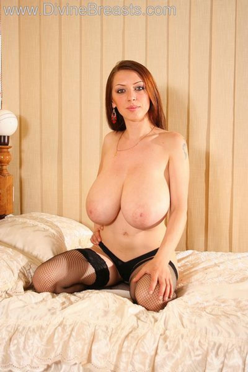 image Hot mature brunette undresses and slides fingers inside her shaved pussy