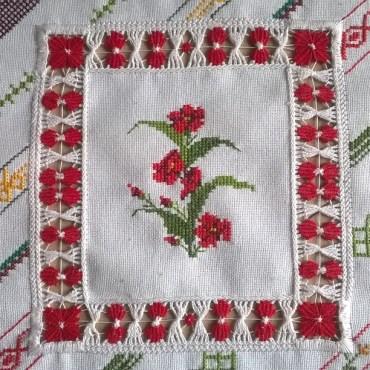 Labor en tela de semihilo bordada a punto de cruz y vainicas.