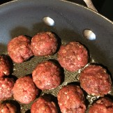 Spiced meatballs cooking in a sauce pan