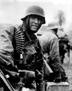 A Nazi soldier, heavily armed, carries ammunition boxes forward with companion in territory taken by their counter-offensive in this scene from captured German film. Belgium, December 1944.