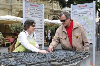Visitante cego tateia réplica do centro antigo de Erfurt com auxílio de guia no Mercado de Peixes