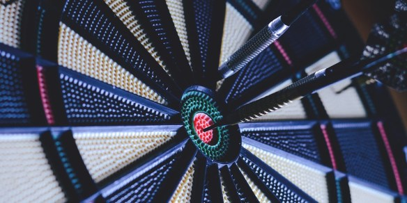 a photo of a dartboard with a dart in the center symbolizing us trying to live in the center of God's will