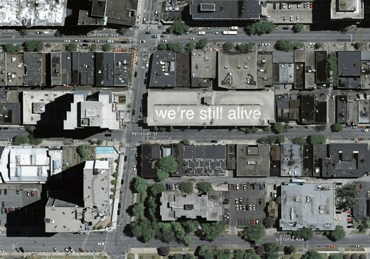 we're still alive: a message to the world, annotating Windsor on the rooftops of parking garages, by Broken City Lab