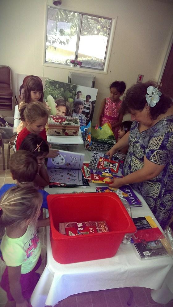 """13 септември 2014 г. Водещата занятията в Школата по Родолюбие """"Златната ябълка"""" г-жа Гаяне Яхджиян (Гая) показва новите учебни помагала на българските малчугани."""