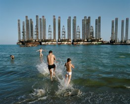 Local boys splash in the Caspian waters, in the shadow of oil rigs. Sixov Beach, Baku, Azerbaijan.