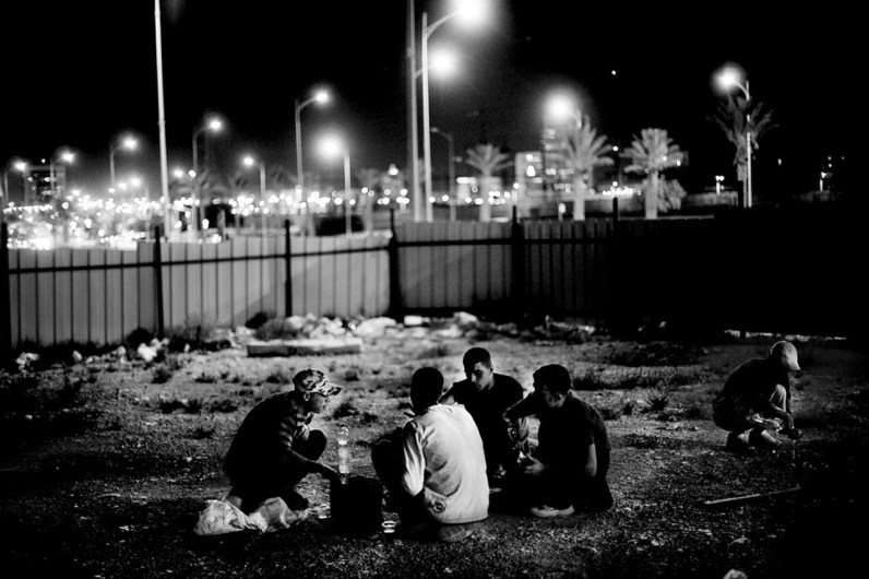 A group of Palestinians teenagers, who stay and work illegally having dinner at one of the many spots where they sleep at night. Beer Sheva City.