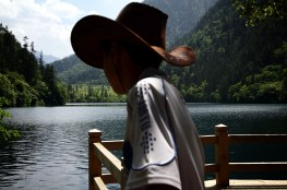 A young boy in a cowboy hat looks out onto one of the many lakes that make up the Jiuzhaigou Nature Reserve in northern Sichuan. Giant Pandas used to be found in the forested mountains of the region up until 10 years ago. Increasing visitor numbers since being awarded World Heritage status has since caused all remaining pandas to flee the region.