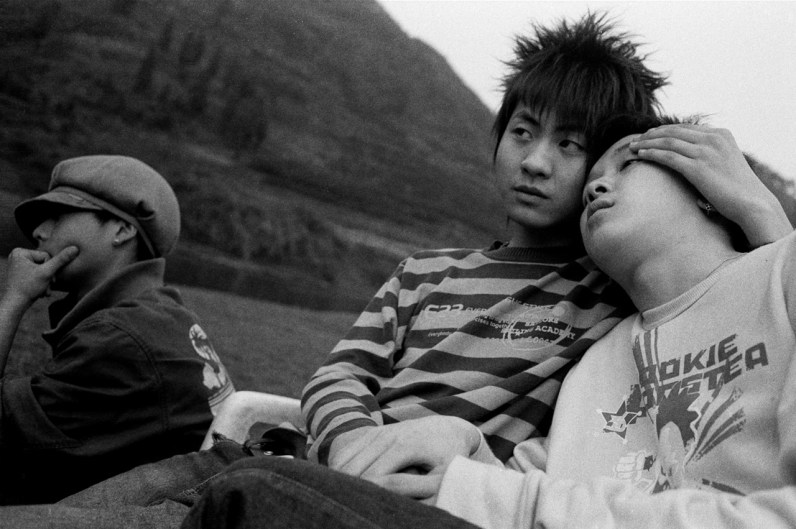 Openly gay teenagers embrace at an afternoon picnic in Xiangxi, China 2006.