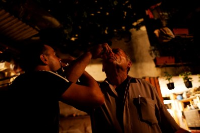 Men drinking their homemade brandy in the Serbian village of Velika Hoca, Kosovo.