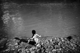 Ecuador, Amazon. December 2011. Anthony, on the bank of a river near his home. Anthony is an eleven years old kid who suffers from birth defects; he can only walk with their knees. For the kids the river is essential in their life, it is the place to play and bathe. People know that water is polluted by oil industry but the river is the only source of water that is also used to cook and to wash clothes.