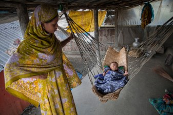 Rani Begum is 15 years old who was married at the age of 12, stands beside her child in Shyamnagar, Satkhira. Natural disasters in Bangladesh and the lack of an adequate government safety net for families affected by them, compound the poverty that drives child marriage. Bangladesh is one of the countries most vulnerable to the effects of climate change. The regular and severe natural hazards that Bangladesh already suffers from – tropical cyclones, river erosion, flood, landslides and drought – are all set to increase in intensity and frequency as a result of climate change. Sea level rise will increasingly inundate coastal land in Bangladesh and dramatic coastal and river erosion will destroy lands and homes. These and the many other adverse effects of climate change will severely impact the economy and development of the country.One of the most dramatic impacts will be the forced movement of people throughout Bangladesh as a result of losing their homes, lands, property and livelihoods to the effects of climate change. While it is impossible to predict completely accurate figures of how many people will be displaced by climate change, the best current estimates state that sea level rise alone will displace 18 million Bangladeshis within the next 40 years. The vast majority of these people will be displaced within Bangladesh – not across international borders – presenting the Government with enormous challenges, particularly when it comes to finding places to live and work for those displaced.