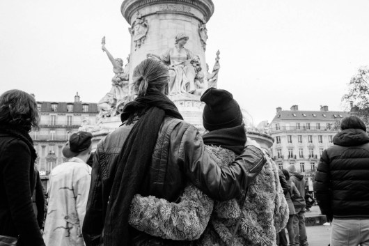 A couple standing in front of the statue in place de la Republique