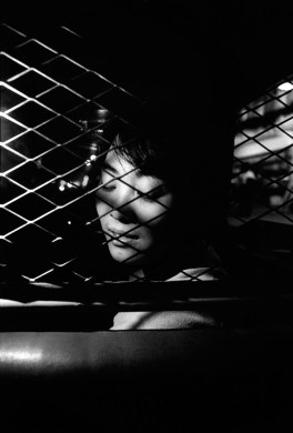 """I like to feel close to the people I photograph. I want to establish a kind of trust and intimacy with them. This young woman was sitting in the front of a cab I boarded during one of my several trips to Guangzhou, China, in 1992. The safety grating protecting the driver divided us. She was really beautiful. Her sultry features were enhanced by the night lights, like in a movie. I'm sure I found the metal mesh annoying when I decided to take a picture of her, but its pattern created interesting contrasts on her face. Also, it prevented me from getting closer, perhaps too close, triggering some reaction in her, maybe a smile, or a self-conscious laugh. She was nearby and yet unreachable. She was so close, yet so far. Untouchable. That is how I remember the moment, but my memory is failing me here. Was she just another passenger, a stranger, or were we riding the cab together? The element of mystery, noticeable and enduring, is what still attracts me in that picture. I don't know anything about her, yet I was close to her then."" — Patrick Zachmann"