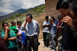 A man, 30, center, reunited with his biological father and his family after being separated for 30 years during the civil war, in the Ixil province, Guatemala. They pray after the formal reunion. Many indigenous became evangelicals during the civil war to keep from being accused of supporting leftist guerrillas. At the time, the military dictator and president, Efrain Rio Montt, was also an evangelical preacher.