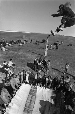 In mid-June, 1991, 63-year old whaling captain Luke Koonook is tossed high into the air at the three day whale feast of Qagruq. The blanket is made from the bearded seal skins that covered his umiak, the pulling handles from his harpoon rope. Tikigaq.