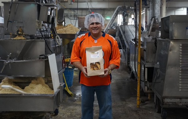 Rich Schneider holds a bag of tortilla chips in the manufacturing plant. (Amy DiPierro)