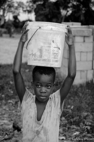 carrying a bucket of water, Ghana, Atsiekpie, village