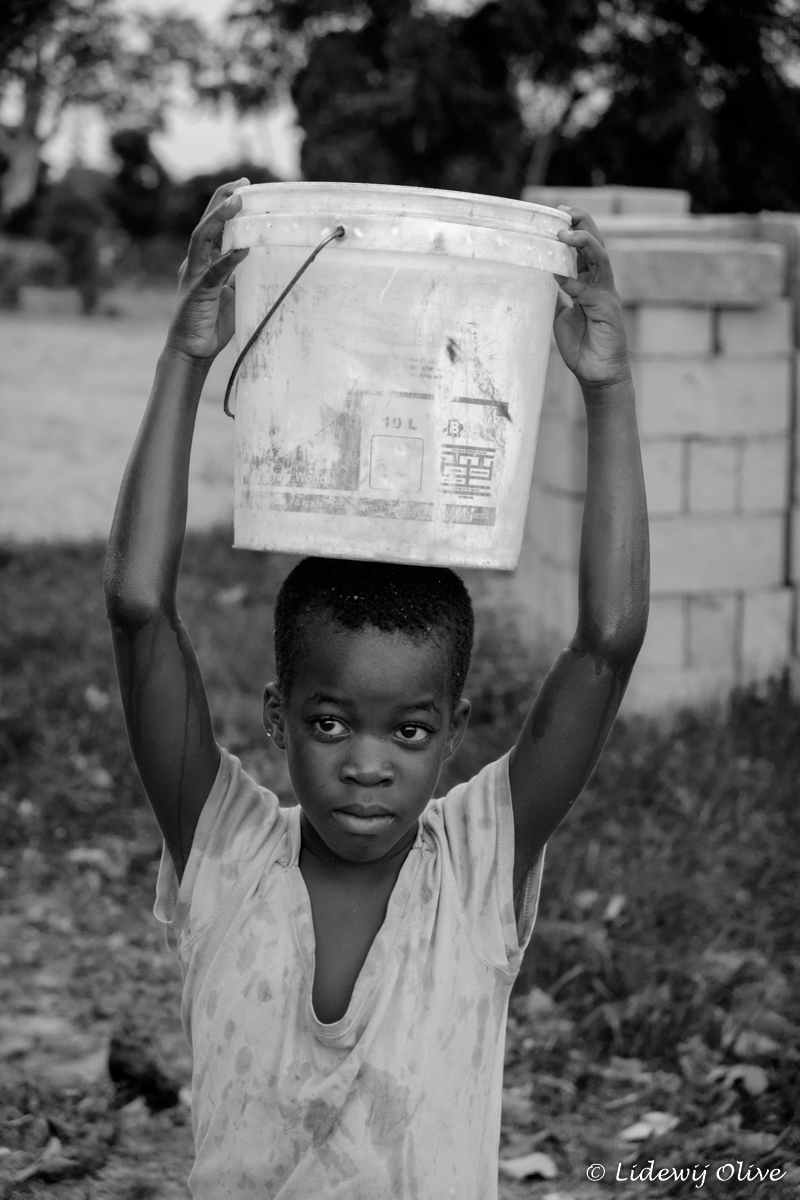 carrying a bucket of water, Ghana, Atsiekpie, village