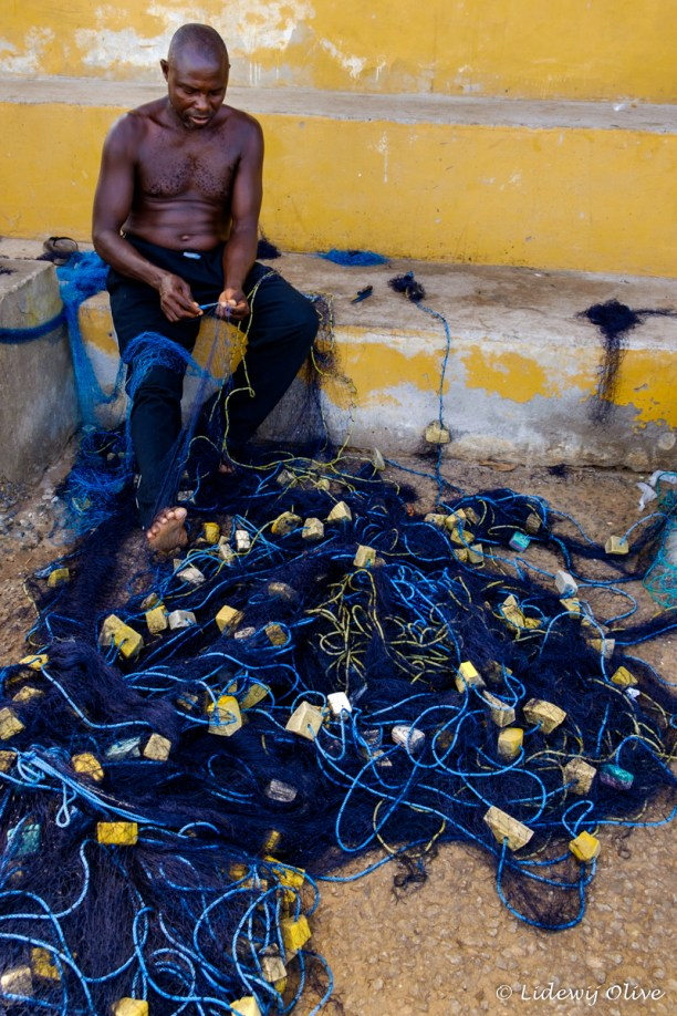 fisherman untangling the net in Elmina, Ghana