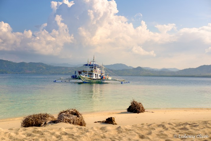 Out boat seen from an island with beautiful white sand