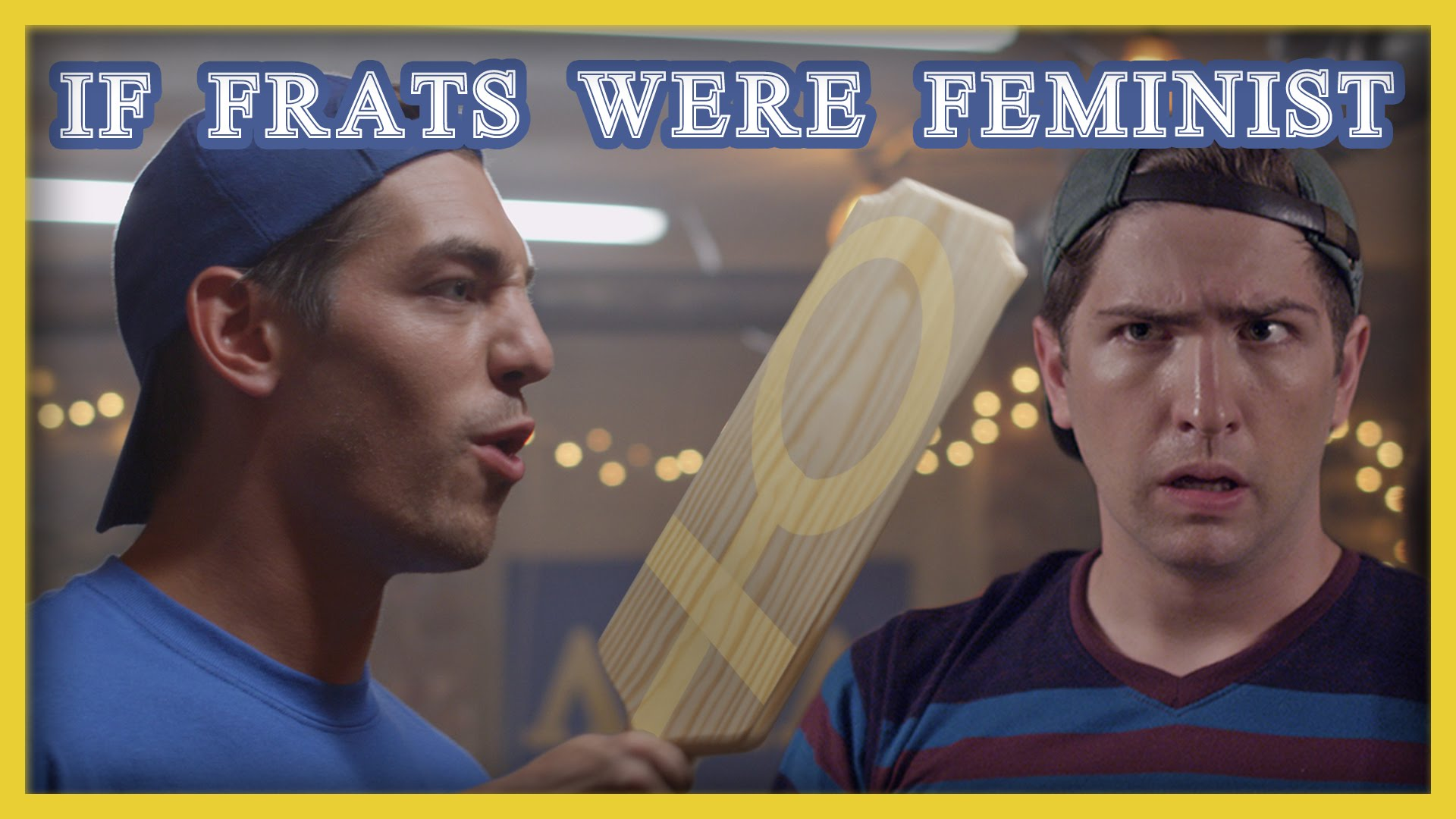"""Two people , male presenting, posed as members of a fraternity. The person on the right holds what looks to be a paddle with the symbol of the female sex highlighted in yellow. Bold text """"If Frats Were Feminist"""" spans the top  of the image."""