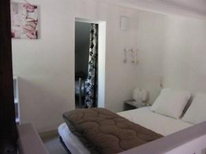 Chambre parentale avec lit en 140 cm, étagère de rangement, table de chevet-lampe.