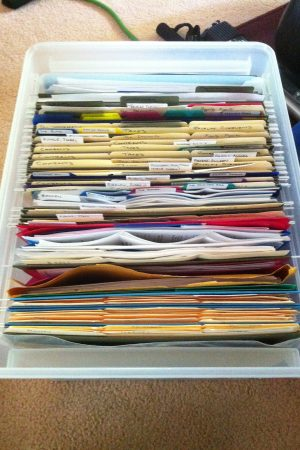 A file box with dozens of neatly labeled, colour-coded files