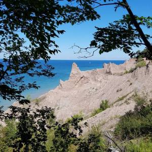 Peeking through the trees at Chimney Bluffs from the trail.