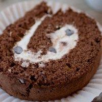 Rotolo al cacao con bagna al caffè, farcito con panna e gocce di cioccolato