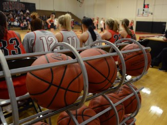 The women's basketball team sits on the bench, waiting to take the court. | Photo by Ebbie Davis