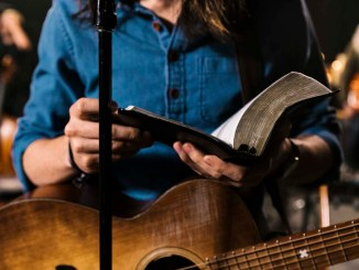 Worship leader holding guitar and Bible | Submitted photo