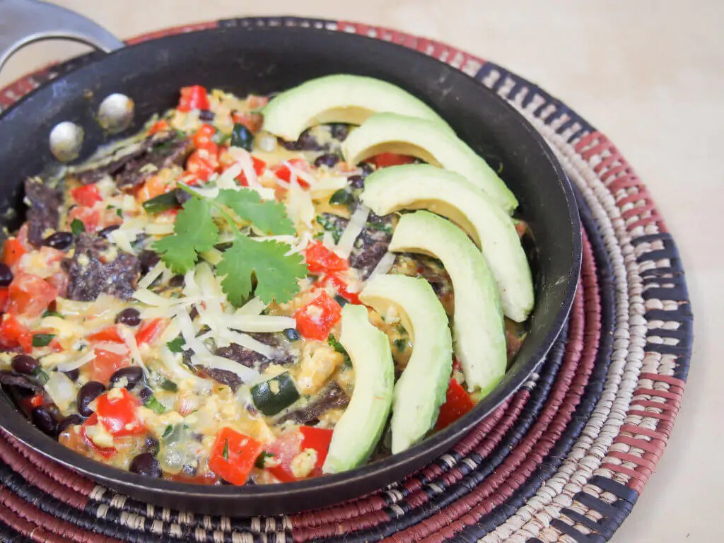 Tex Mex migas are a delicious, easy dish made with eggs, corn tortillas, cheese & salsa ingredients, here freshened up with cilantro, black beans & peppers.