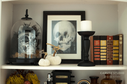 Halloween bookshelf display with skull, books and pumpkins