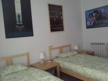 dos camas individuales y mesitas de noche con lámparas