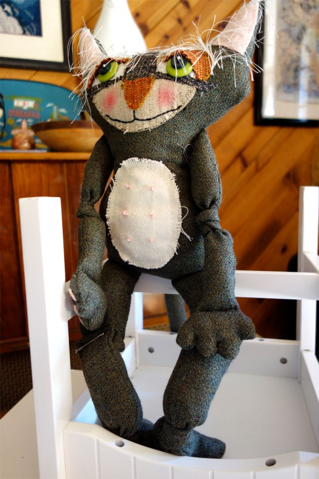 Old whimsical cat doll sits on upside down chair on table top.